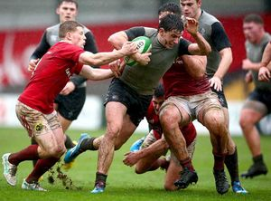 Munster's John Poland and Evan Mintern tackle Hugh Keenan of Ireland U20s.
