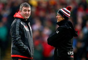 Head coaches Anthony Foley and Less Kiss chat before the game.