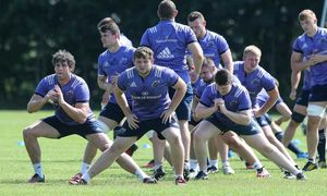 Dave O'Callaghan, academy prop Liam O'Connor and the squad stretch before the session commences.