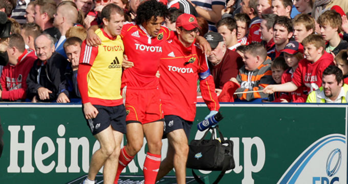 Doug Howlett is helped off by Munster's Tom Comyns and Neil Tucker