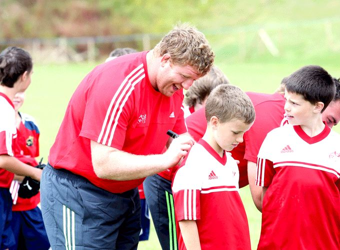 Stephen Archer signs autographs for the participants at last week's camp in Bandon RFC.