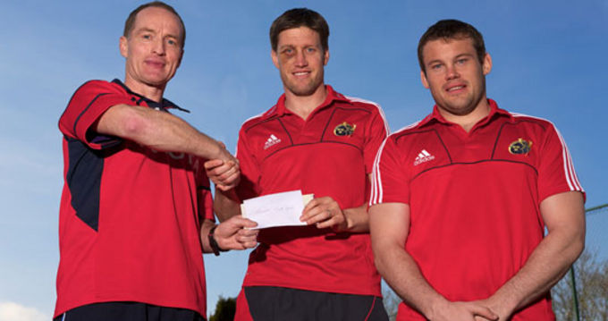 Paul Sheridan handing over the cheque to Ronan O'Gara and Denis Fogarty